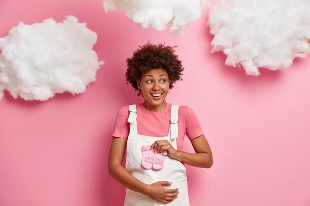 Uśmiechnięta piękna młoda kobieta cieszy się z ciąży, cieszy się z urodzenia dziecka, trzyma skarpetki na brzuchu, nosi luźne ubrania dla ciężarnych, patrzy na bok, stoi w domu. koncepcja szczęśliwego macierzyństwa