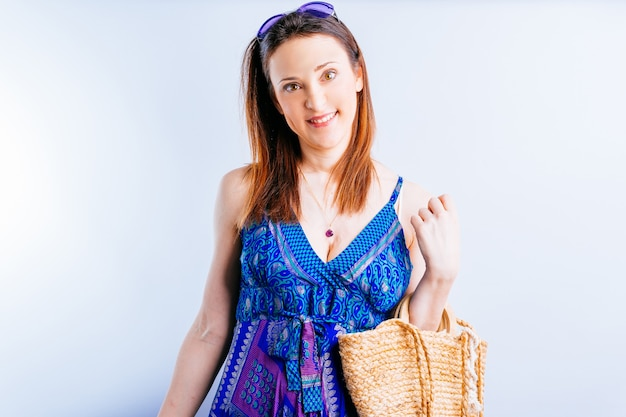 Uśmiechnięta piękna młoda kobieta czeka z letnią sukienką i torbą plażową na białym tle