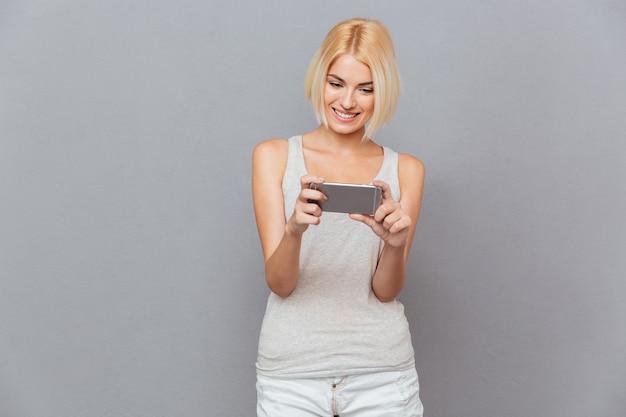 Uśmiechnięta piękna młoda kobieta korzystająca z telefonu komórkowego na szarej ścianie
