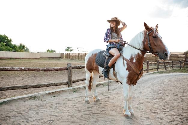 Uśmiechnięta piękna młoda kobieta kowbojka siedzi i jeździ konno na ranczo
