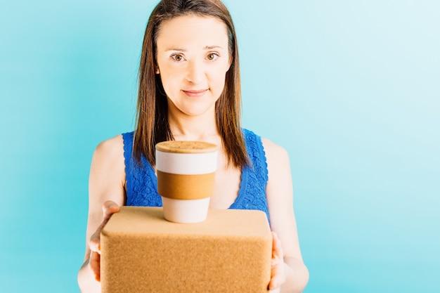 Uśmiechnięta piękna młoda kobieta na niebieskim tle trzymająca filiżankę kawy wielokrotnego użytku na cegle do jogi
