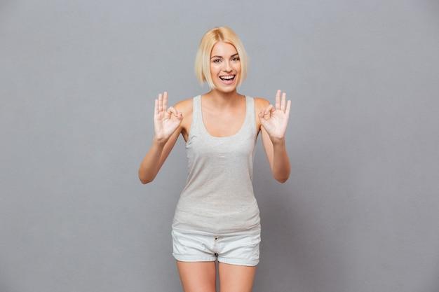 Uśmiechnięta piękna młoda kobieta pokazująca znak ok obiema rękami nad szarą ścianą