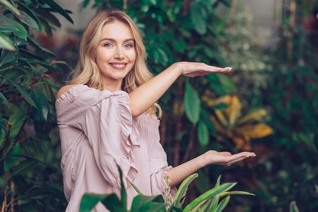 Uśmiechnięta piękna młoda kobieta pokazuje coś na palmach jej ręki w ogródzie