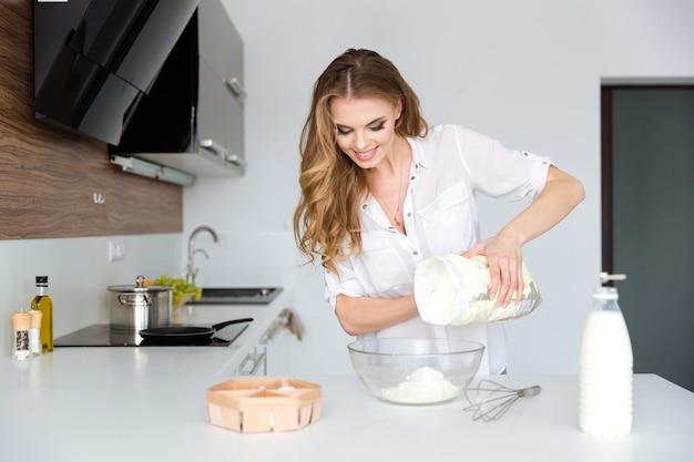 Uśmiechnięta piękna młoda kobieta przygotowuje ciasto i używa białej mąki w kuchni