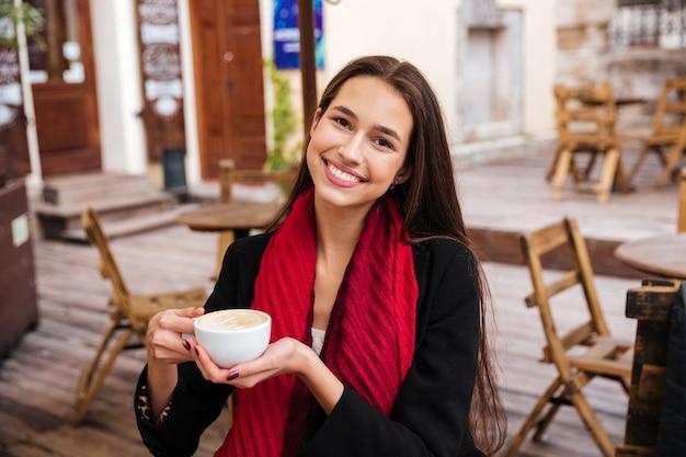 Uśmiechnięta piękna młoda kobieta siedzi i pije kawę w kawiarni na świeżym powietrzu