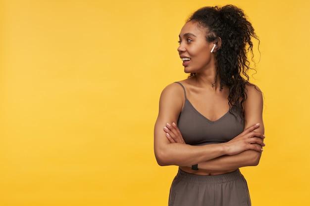 Uśmiechnięta piękna młoda kobieta sportowca stojąca z rękami skrzyżowanymi za pomocą bezprzewodowych słuchawek i odwracająca wzrok w bok na copyspace na białym tle nad żółtą ścianą