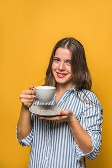 Uśmiechnięta piękna młoda kobieta trzyma filiżankę i spodeczek w rękach