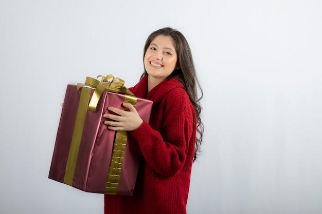 Uśmiechnięta piękna młoda kobieta trzyma pudełko na prezent bożonarodzeniowy.