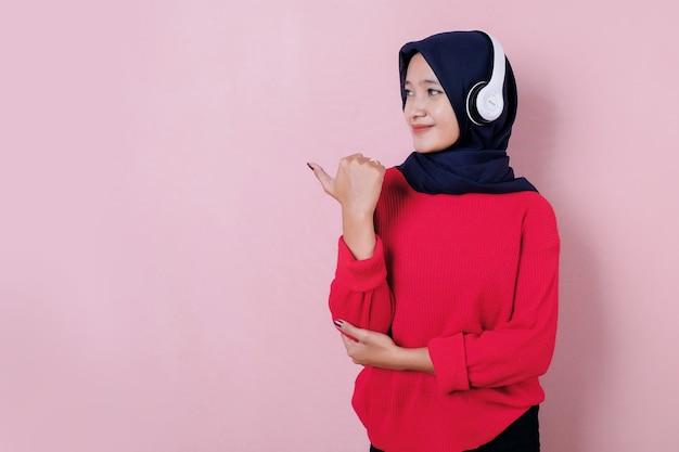 Uśmiechnięta piękna młoda kobieta ubrana w czerwoną koszulkę co kciuk za pomocą słuchawki