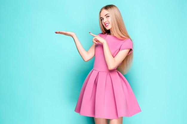 Uśmiechnięta piękna młoda kobieta w różowej mini sukni pozować, przedstawia coś