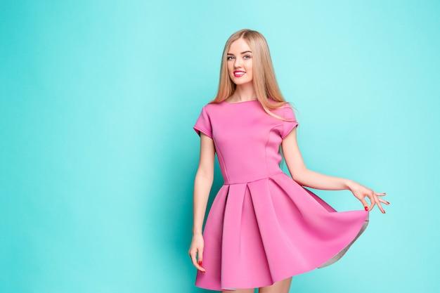 Uśmiechnięta piękna młoda kobieta w różowej mini sukni pozuje przy studiiem