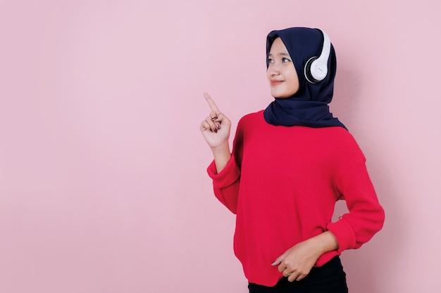 Uśmiechnięta piękna młoda kobieta, wskazując coś na sobie czerwoną koszulkę za pomocą słuchawek