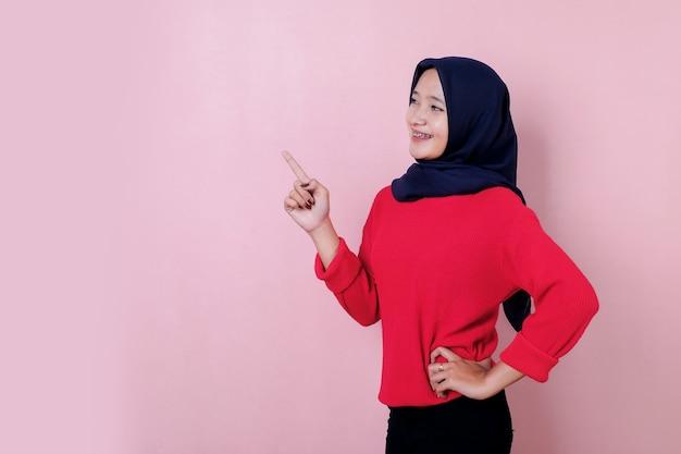 Uśmiechnięta piękna młoda kobieta, wskazując coś na sobie czerwoną koszulkę