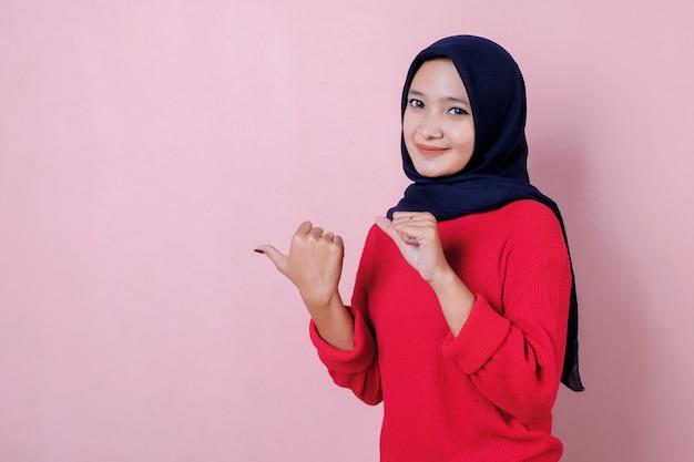 Uśmiechnięta piękna młoda kobieta, wskazując odrobiną kciuka na sobie czerwoną koszulkę