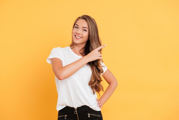Uśmiechnięta piękna młoda kobieta wskazuje copyspace.
