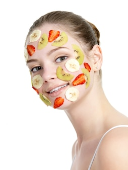 Uśmiechnięta piękna młoda kobieta z maską owoców na jej twarzy na białym tle