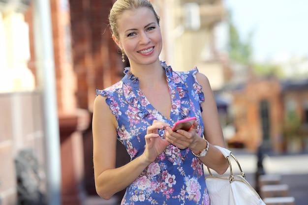 Uśmiechnięta piękna młoda kobieta z telefonem w ręku