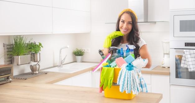 Uśmiechnięta piękna pani stojąca za biurkiem w nowoczesnej kuchni, wystrojona do sprzątania z detergentami i dywanikami przed nią.