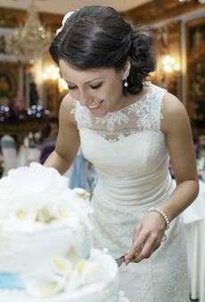 Uśmiechnięta piękna panna młoda ciie ślubnego tort