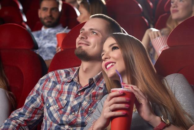 Uśmiechnięta piękna para obejmując i oglądając film w kinie.