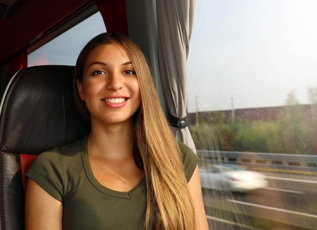 Uśmiechnięta piękna podróżnik kobieta w autobusie patrząc na kamery. koncepcja podmiejskich transportu publicznego.