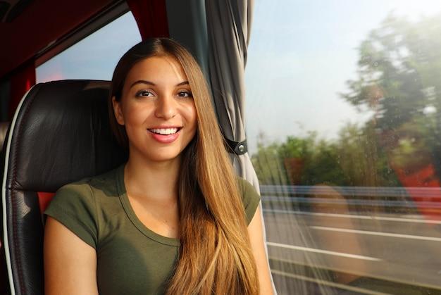 Uśmiechnięta piękna podróżnik kobieta w autobusie patrząc na kamery.