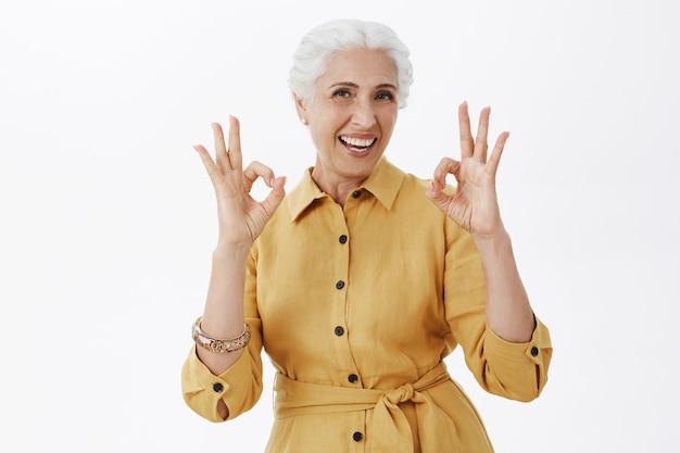 Uśmiechnięta piękna starsza kobieta pokazująca dobry gest, aprobuje i lubi pomysł, gwarantuje obsługę