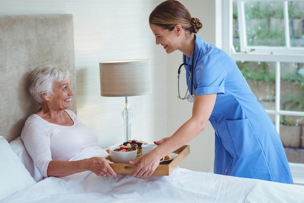Uśmiechnięta pielęgniarka daje jedzeniu starsza kobieta
