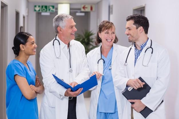 Uśmiechnięta pielęgniarka i lekarki dyskutuje nad schowkiem