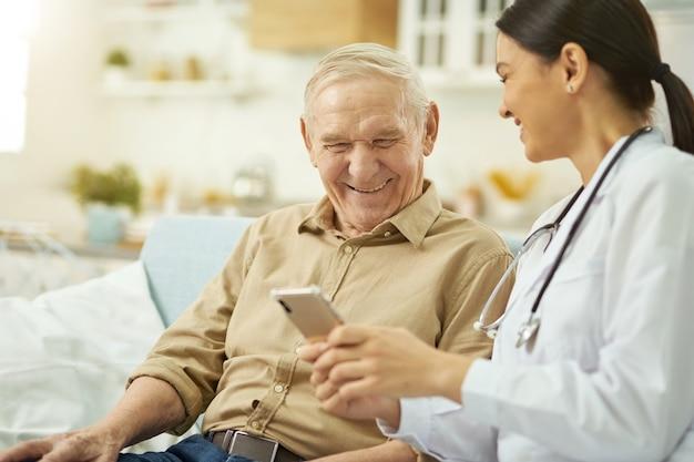 Uśmiechnięta pielęgniarka i senior siedzący na kanapie i korzystający z telefonu