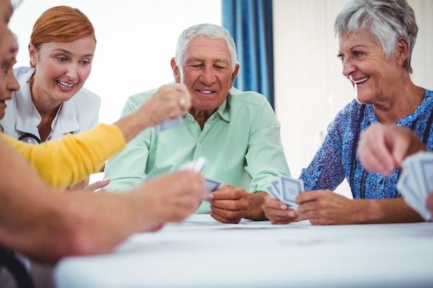 Uśmiechnięta pielęgniarka i seniorzy ludzie grają w karty