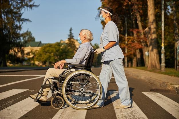 Uśmiechnięta pielęgniarka pomagająca starszemu mężczyźnie chodzić po ulicy miasta