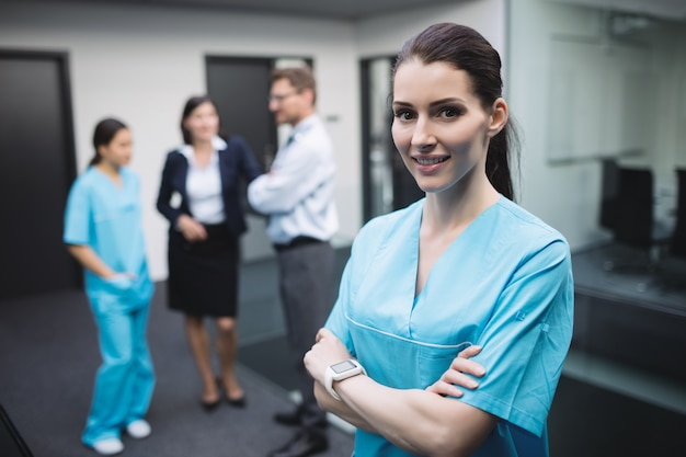 Uśmiechnięta pielęgniarka stojąca z rękami skrzyżowanymi