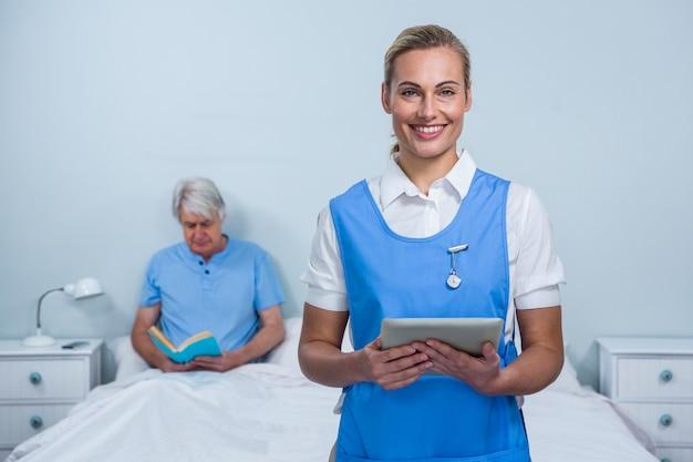 Uśmiechnięta pielęgniarka trzyma cyfrową pastylkę przy szpitalem