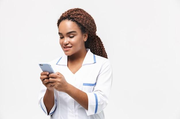 Uśmiechnięta pielęgniarka w płaszczu medycznym trzymająca i używająca telefonu komórkowego odizolowanego od białej ściany