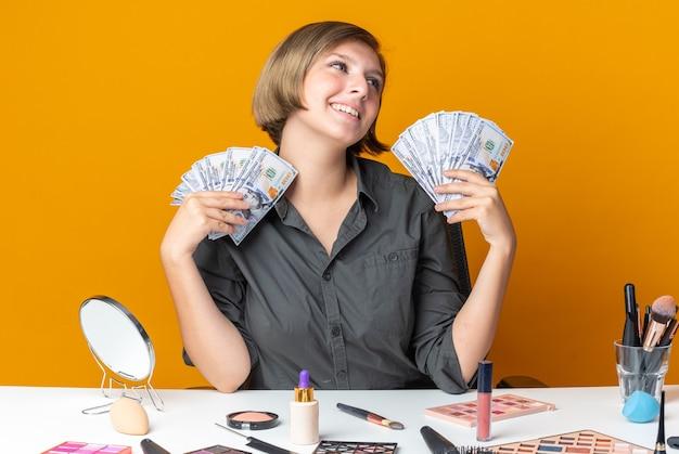 Uśmiechnięta pochylająca się głowa piękna kobieta siedzi przy stole z narzędziami do makijażu trzymającymi gotówkę