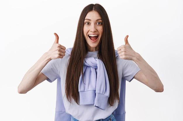 Uśmiechnięta podekscytowana dziewczyna pokazuje kciuki z aprobatą, zgadza się i lubi dobry produkt, chwali niesamowitą pracę, doskonałą pracę lub doskonały wybór, stojąc nad białą ścianą