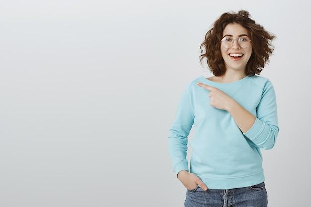 Uśmiechnięta podekscytowana dziewczyna w okularach wskazującym palcem w lewo