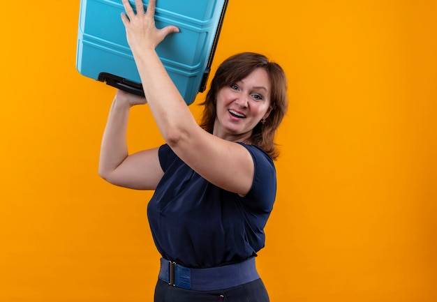Uśmiechnięta podróżna w średnim wieku kobieta podnosząca walizkę na odosobnionym pomarańczy z miejsca na kopię