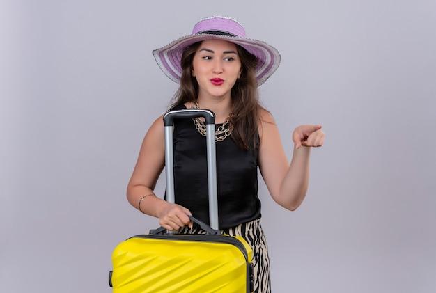 Uśmiechnięta podróżnik młoda dziewczyna ubrana w czarny podkoszulek w kapeluszu, trzymając walizkę i wskazuje na bok na białym tle