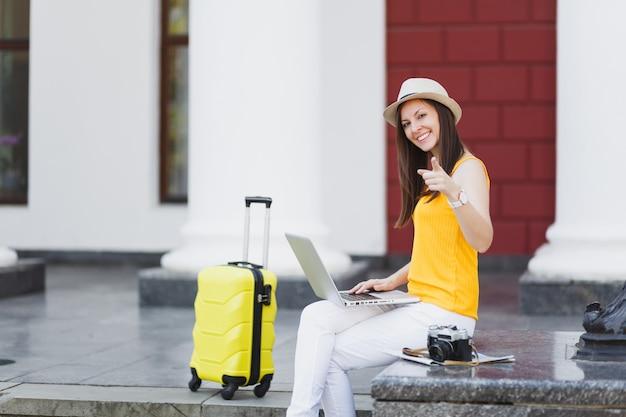Uśmiechnięta podróżnik turysta kobieta w kapeluszu z walizką wskazując palcem wskazującym na aparat, trzymając komputer typu laptop w mieście na zewnątrz. dziewczyna wyjeżdża za granicę na weekendowy wypad. styl życia podróży turystycznej.