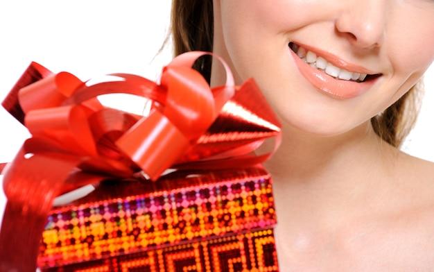 Uśmiechnięta pół twarzy piękna dziewczyna z czerwonym pudełkiem na pierwszym planie