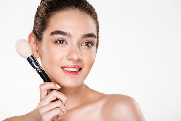 Uśmiechnięta półnaga kobieta ze świeżą skórą trzyma pędzel do makijażu blisko twarzy i odwraca wzrok