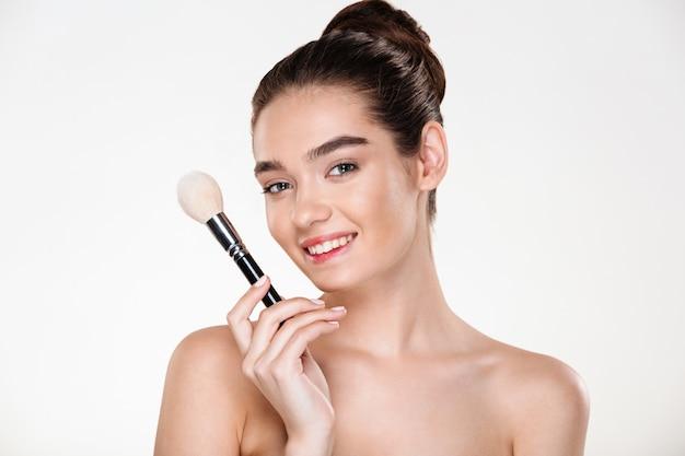 Uśmiechnięta półnaga kobieta ze szczotką do trzymania świeżej skóry do makijażu blisko twarzy z zastosowaniem korektora