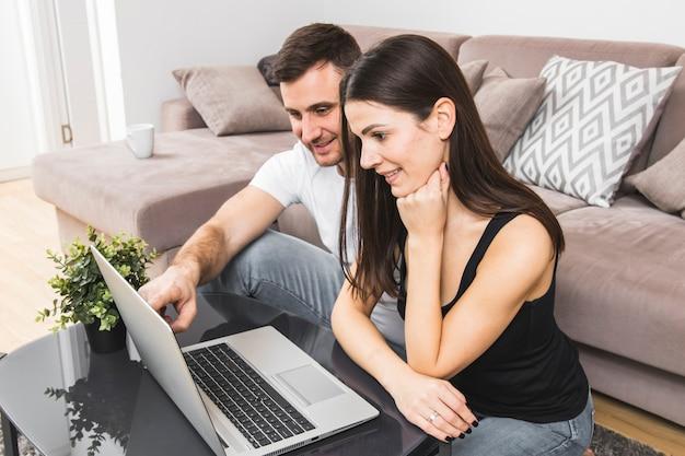 Uśmiechnięta potomstwo para używa laptop w domu