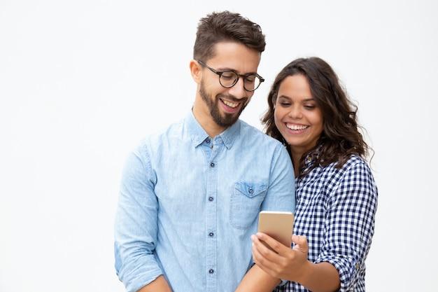 Uśmiechnięta potomstwo para używa smartphone