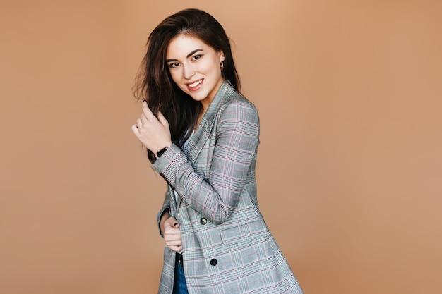 Uśmiechnięta pozytywna brunetka. brązowooka dama w stylowym stroju pozuje w beżowym pokoju.