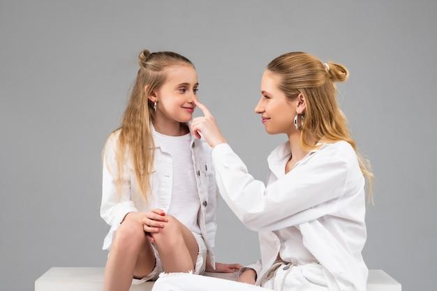 Uśmiechnięta pozytywna długowłosa dama dotykająca nosa swojej małej przyjaciółki palcem wskazującym podczas siedzenia razem