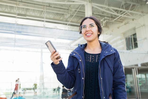 Uśmiechnięta pozytywna dziewczyna używa telefon outdoors