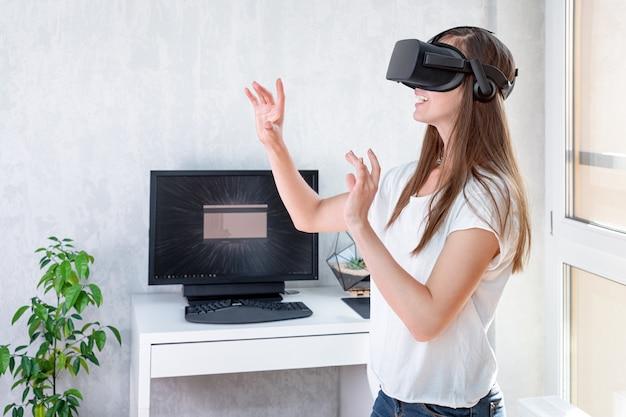 Uśmiechnięta pozytywna kobieta jest ubranym rzeczywistość wirtualna gogle słuchawki, vr pudełko. połączenie, technologia, nowa generacja, koncepcja postępu. dziewczyna próbuje dotykać obiektów w wirtualnej rzeczywistości